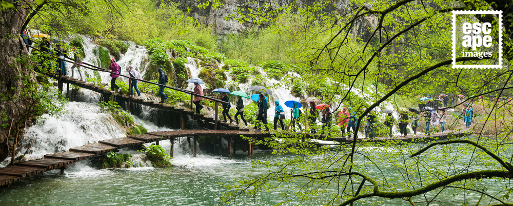 Visitors hide under raincoast and umbrellas at Plitvice Lakes National Park
